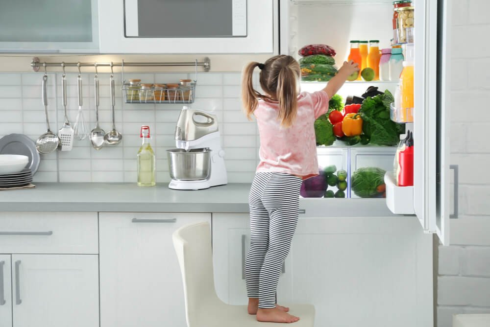 young girl looking in refrigerator freezer
