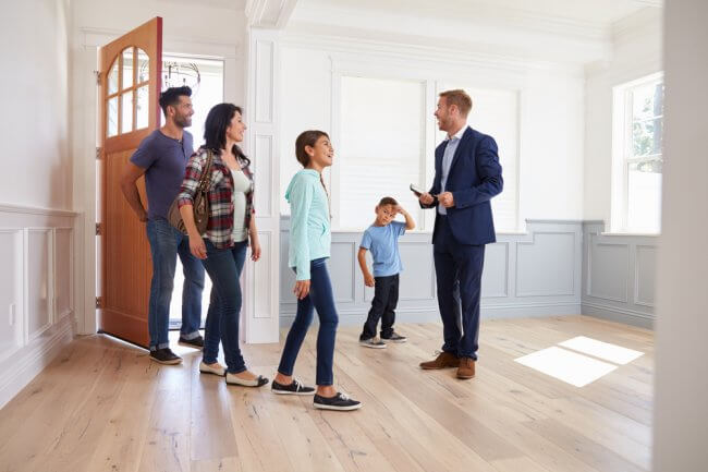 Family entering home for sale with real estate agent