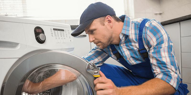man conducting washing machine maintenance