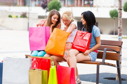 three women sitting on a bench with shopping bags