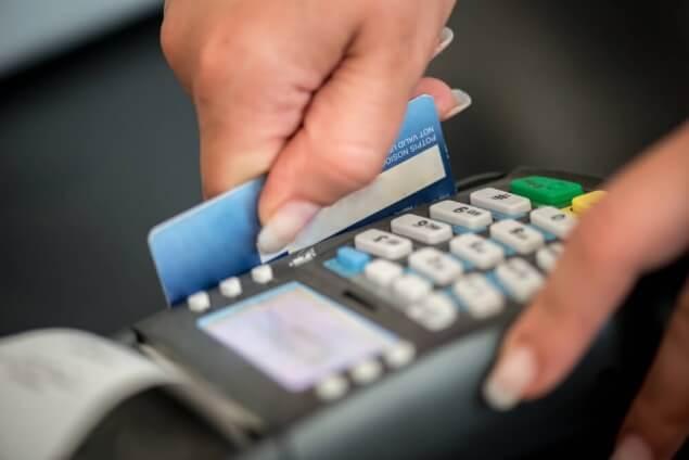 person swiping credit card on eftpos terminal machine