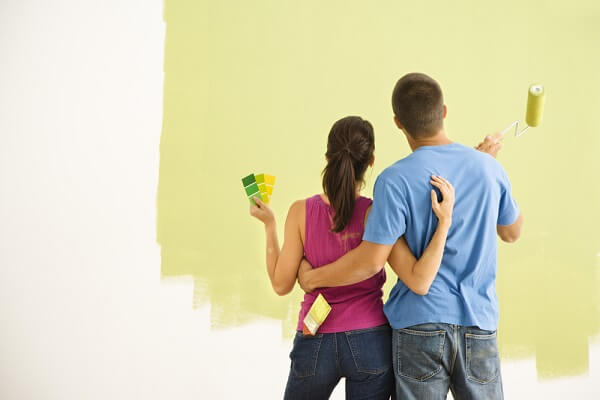 couple painting a wall green