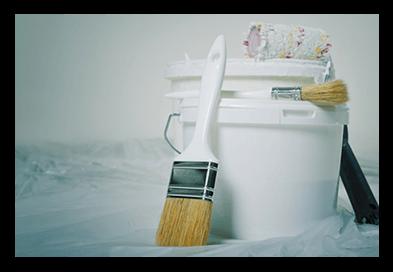 bucket of white paint and paint brush