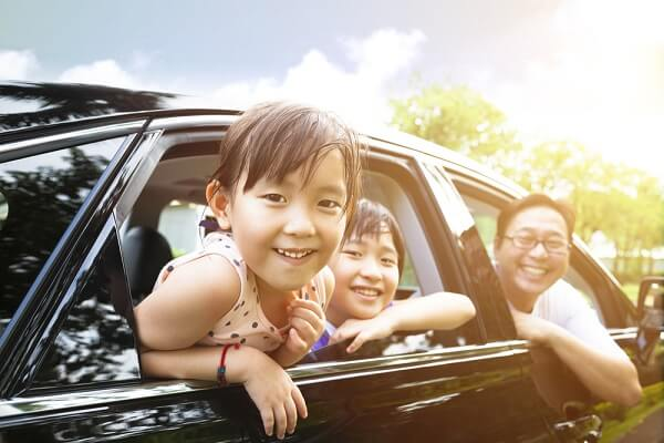 kids and parent looking out the window of a car