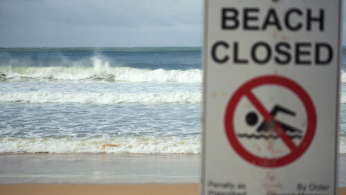 Beach closed sign at beach with waves crashing in background