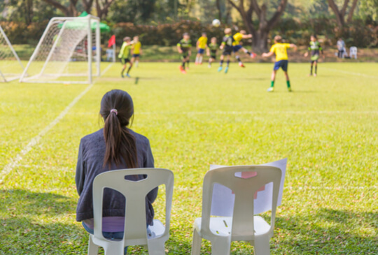mother-sitting-on-the-field-sideline-watching-children-play-sport