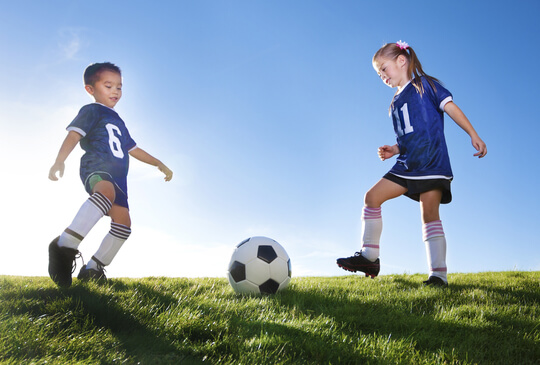 young-boy-and-girl-playing-soccer-on-a-grass-field-in-team-uniform