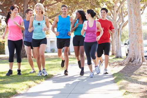 group of runners jog by the road