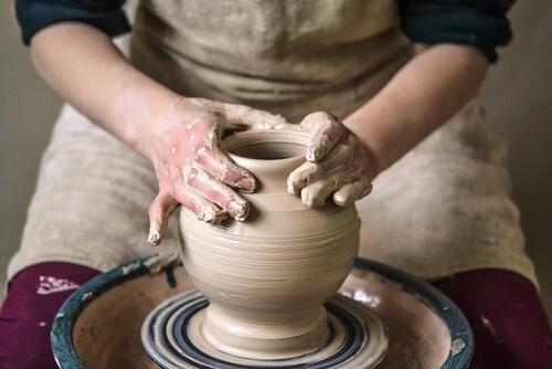 woman sculpting clay jar on pottery wheel