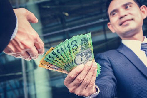 Businessmen passing money, Australia dollar (AUD) banknotes