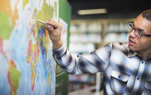 Man pointing and examining world map