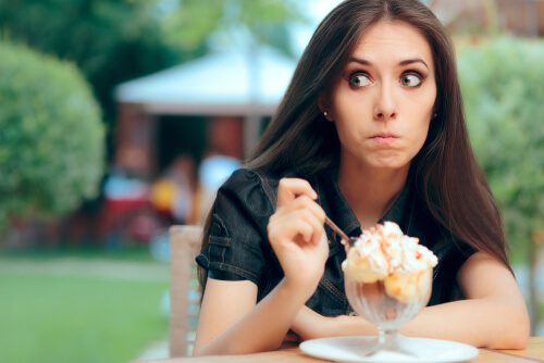 Young woman eating takeaway dessert feeling guilty