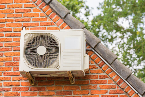 air conditioner unit outside brick wall