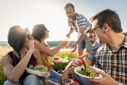 People sitting on the ground eating burgers on plastic plates