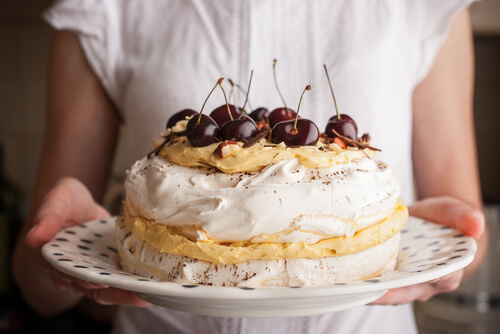 Woman holding plate with pavlova chopped with cherries