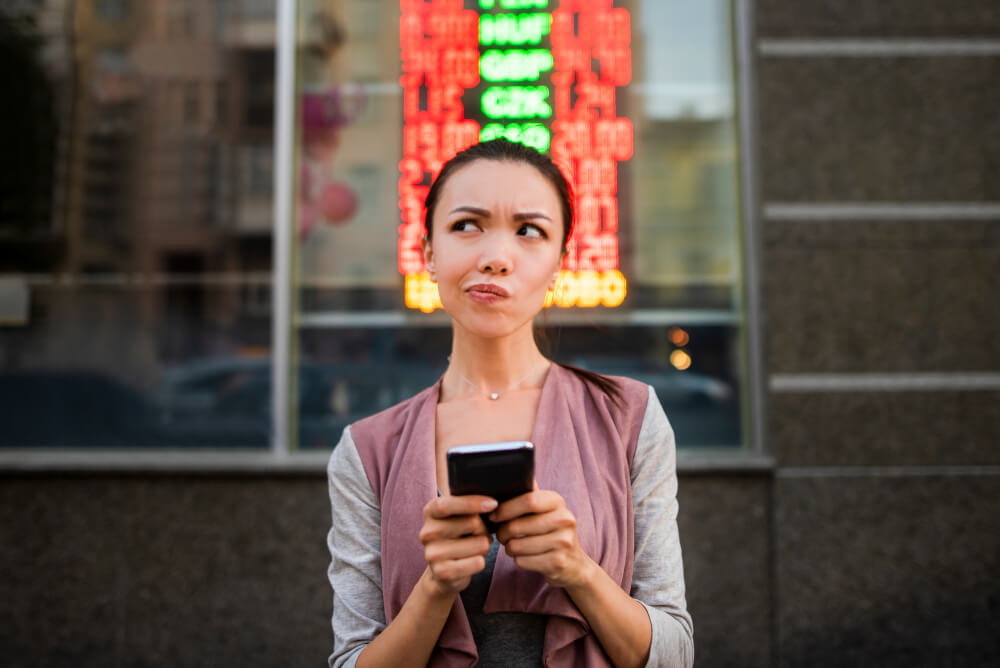 A woman using an application on her smart phone to check currency exchange rates.