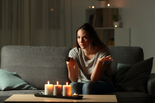 Young woman in power outage at home with candles in living room