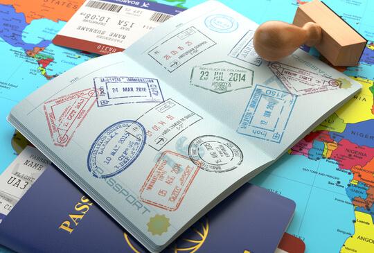 A well-travelled passenger's passport on top of a world map.