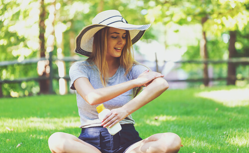 woman wearing hat applies sunscreen at the park