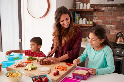 children help their mother prepare food in the kitchen