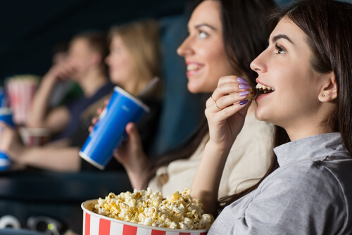 women in a cinema with popcorn and soft drink