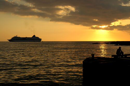 cruise ship on horizon at sunset