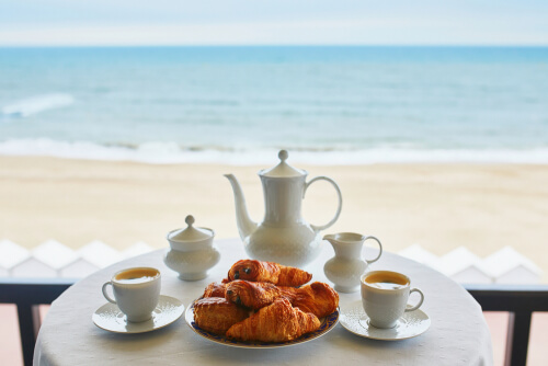 cups of coffee and a plate of pastries by the beach