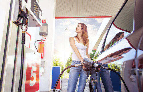 Young woman refueling her car.