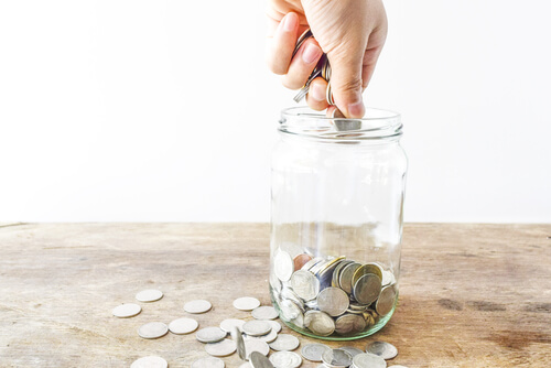 Person making a donation into a coin jar.
