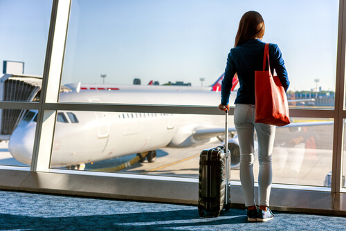 woman with bag and suitcase waiting at the airport