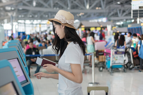 young woman in hat at airport digital check-in