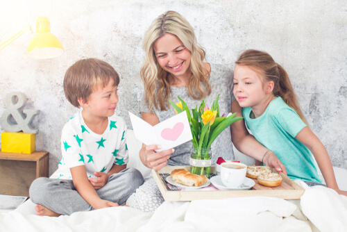 children give their mum breakfast in bed on Mother's Day