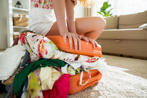 woman sitting on overflowing suitcase