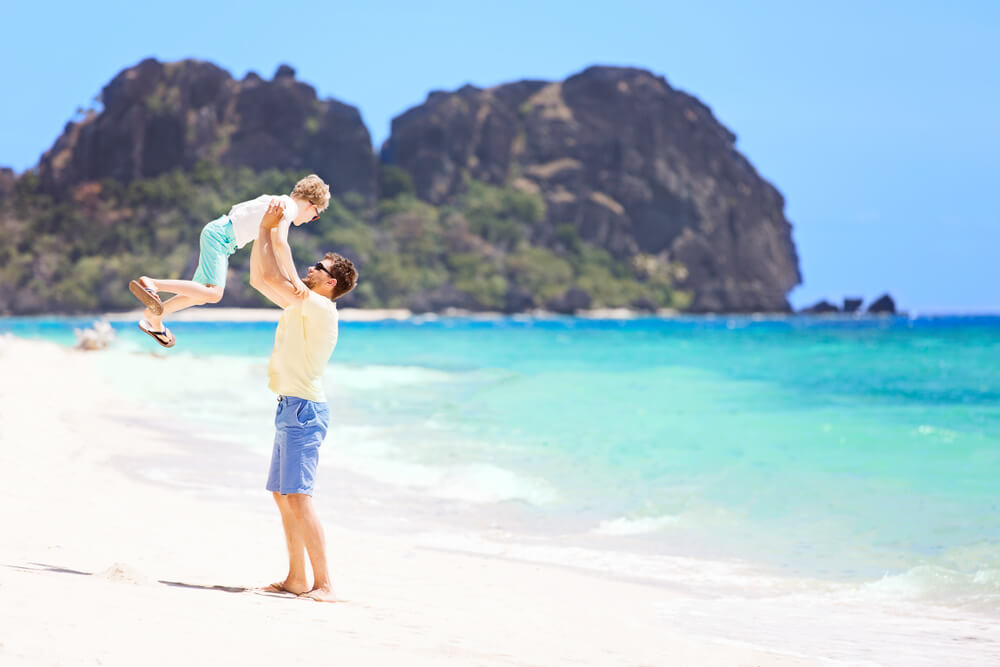 view of tropical beach and father throwing his son high up at fiji
