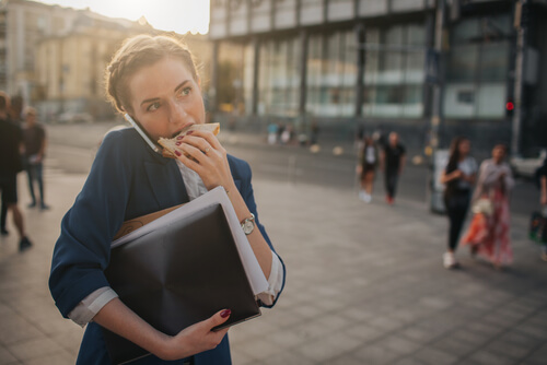 a woman eats a sandwich outside while on a phone call and carrying documents