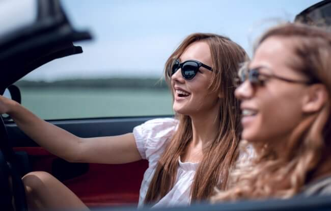 Two women in a convertible car