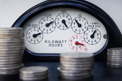an energy meter behind piles of coins