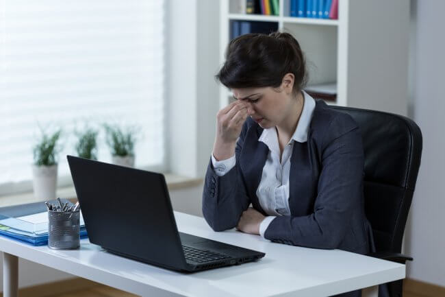 Business woman at her desk pinching her nose in pain