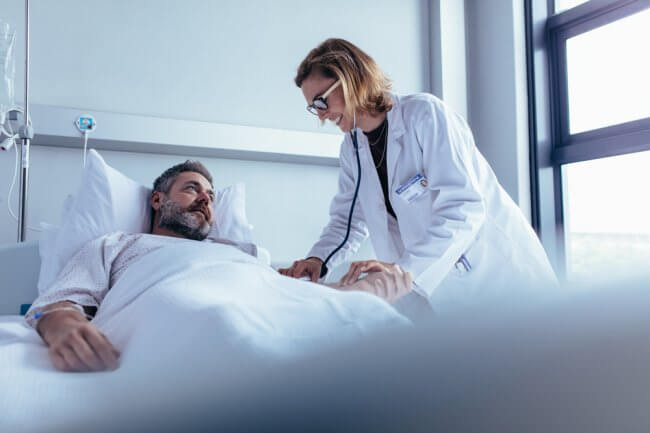 Doctor checking up on a patient in a hospital bed