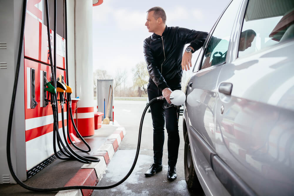 A man filling up his car fuel tank with petrol