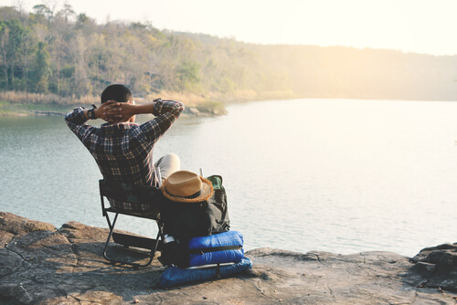a man relaxing on a folding chair next to a lake