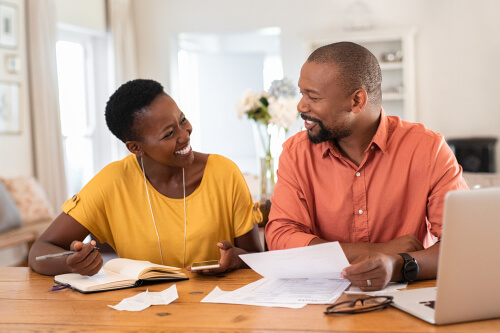 a happy couple going over finances
