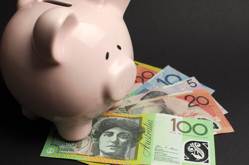 a piggy bank on top of Australian currency