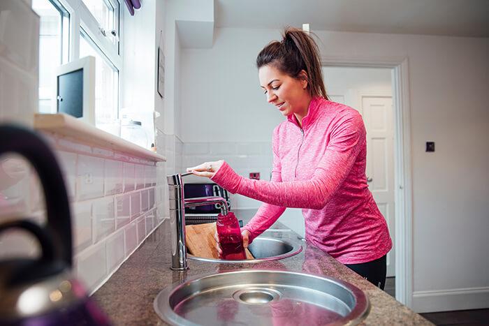 Woman filling water bottle