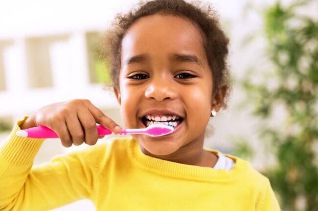Young smiling girl brushing her teeth