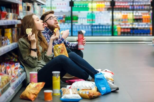 Young couple sitting on shop floor eating junk food