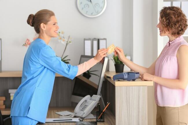 Woman handing credit card to medial receptionist to pay for appointment