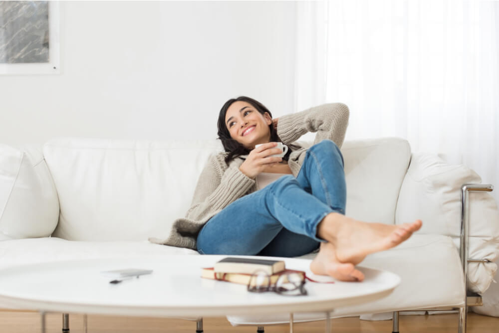 A woman smiling and relaxing on sofa at home with a coffee in hand