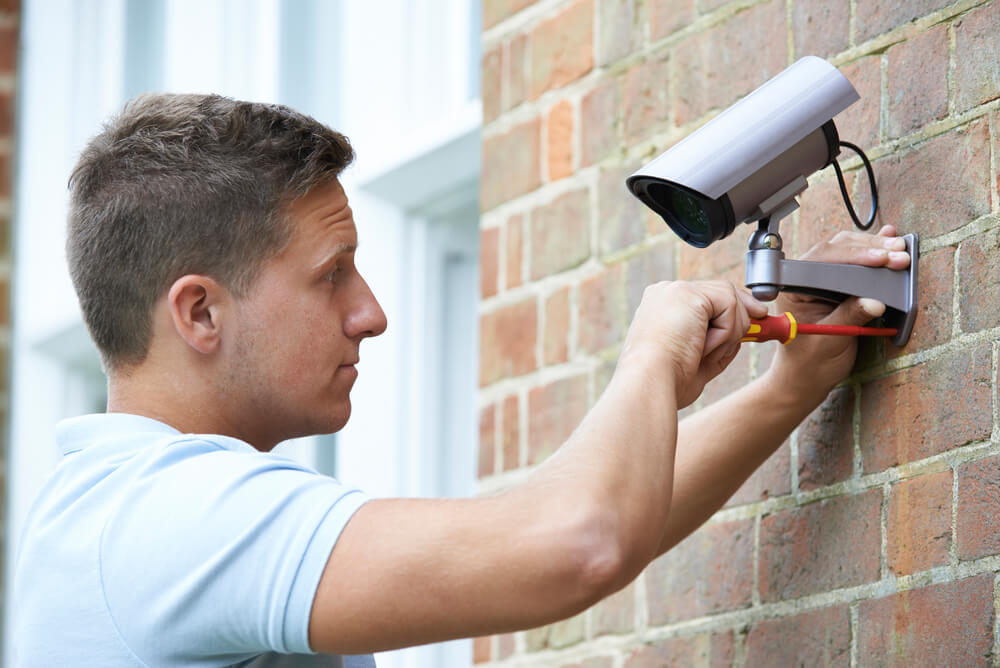 A young man installing security camera to help secure his home against burglary