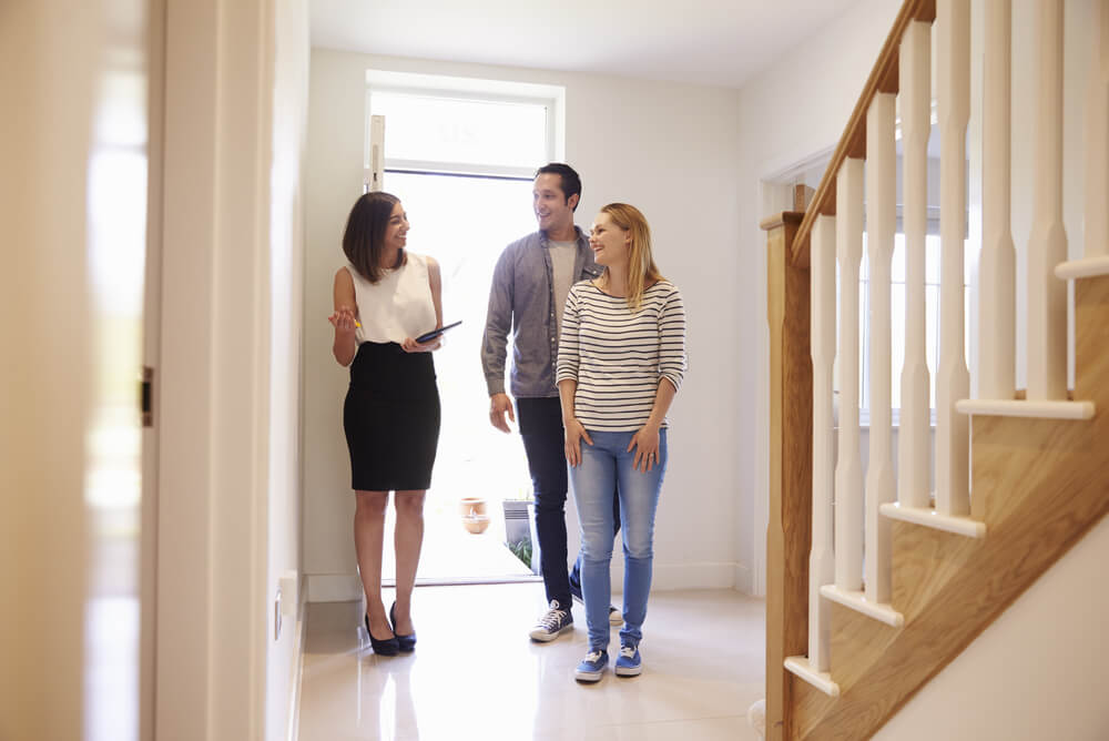 A young property investor couple looking at potential home and asking real estate agent what is landlord insurance